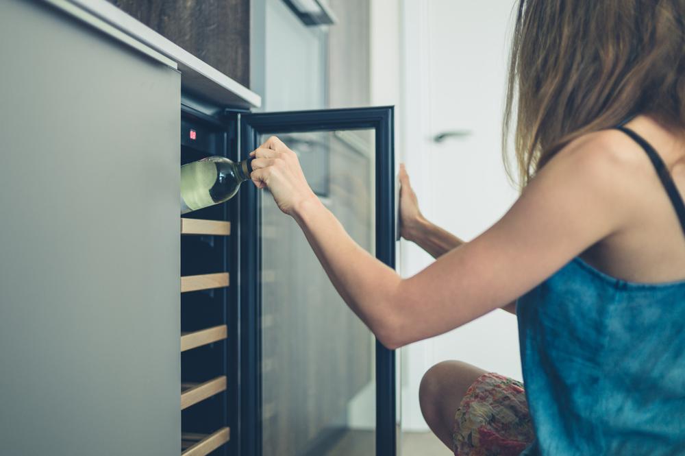 woman opening wine fridge