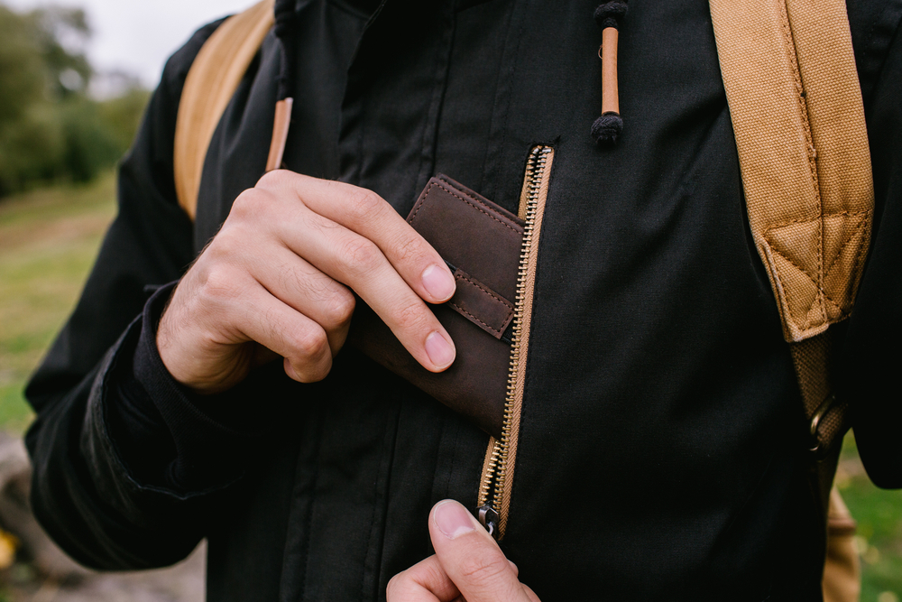 man pulling wallet out of jacket