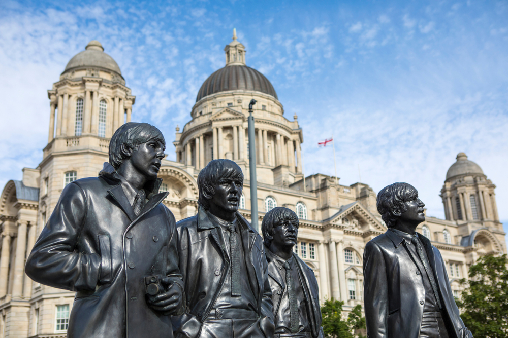 Statues of The Beatles - Paul McCartney, George Harrison, Ringo Starr and John Lennon - with the Port of Liverpool building in the background, in the city of Liverpoo