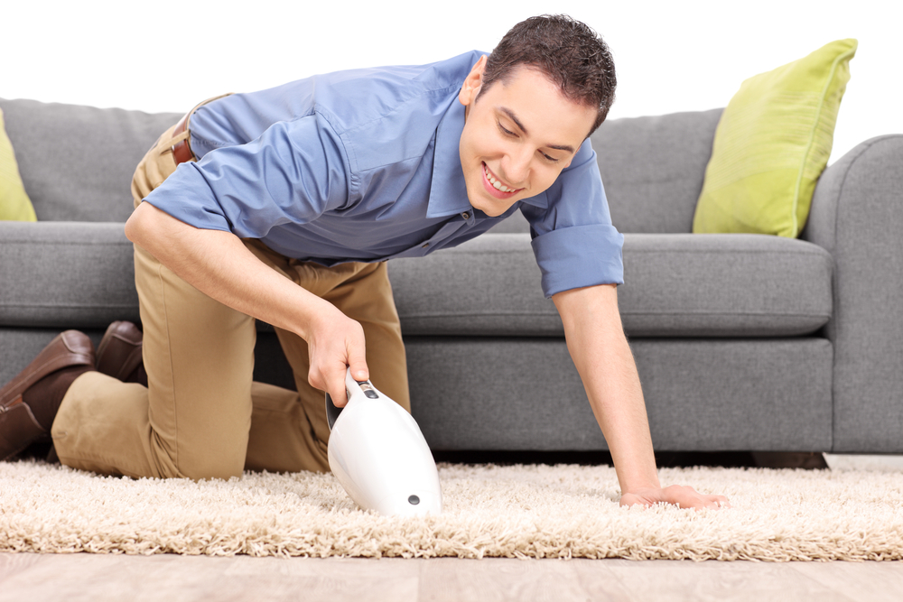 young man vacuuming carpet
